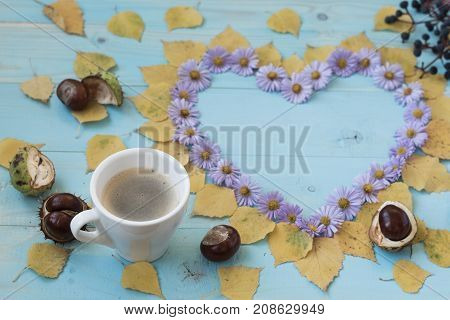 Cup of coffee and symbol of heart with autumn flowers on old wooden blue background. symbol of heart with autumn flowers. old wooden blue background.Concept autumn. autumn theme