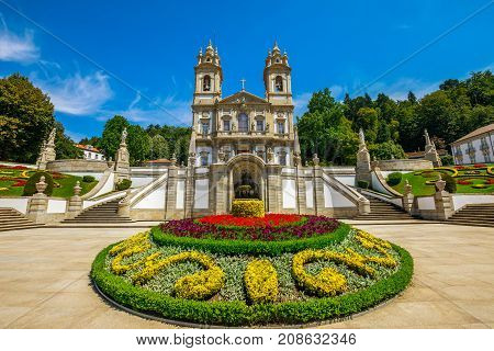 The spectacular facade of the Bom Jesus do Monte Sanctuary in neoclassical style surrounded by flowered gardens in a sunny day. Tenoes near Braga, north of Portugal, Europe.