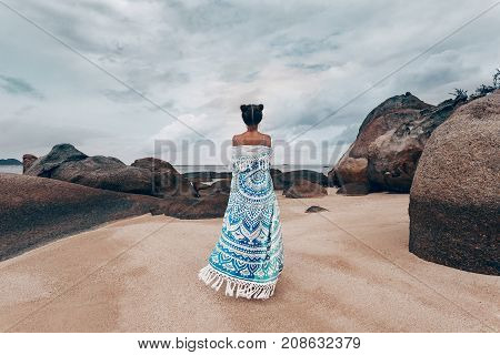 beautiful young woman covered with shawl on the beach