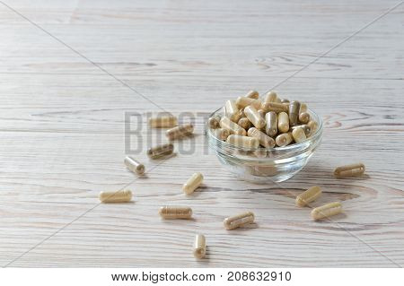 Biologically active supplement in glass bowl on white wooden background. Copy space composition. Selective focus