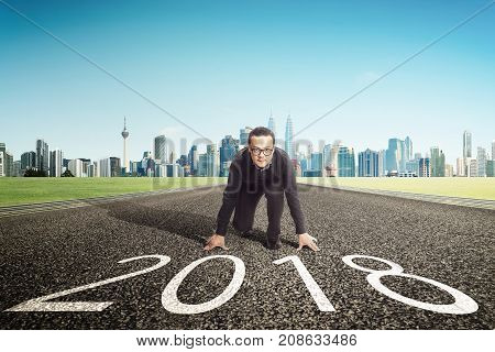New year 2018 young businessman starting position to his career with city skyline background . Determined to start concept .