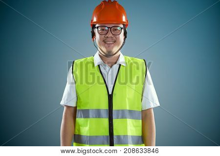 Young asian construction workers in safety helmet on a blue background .