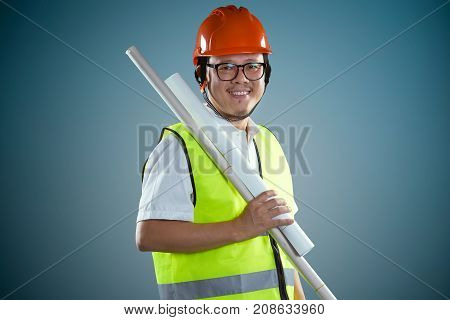 Young asian construction workers in safety helmet and hold the rolled blueprints isolated on blue background .