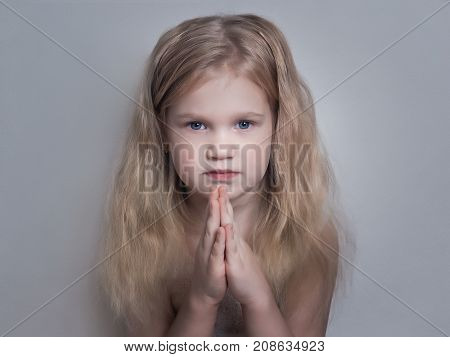 Beautiful little girl folded her hands in a prayerful gesture. The child looks with hope and faith
