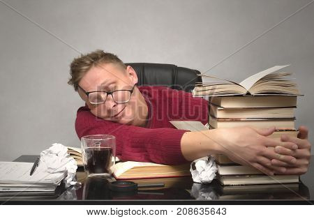 Student man tired of studying and sleeping on desk table with books and crumpled paper pages around. Tired worker. Overworked business man.