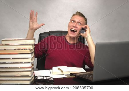 Young happy business man emotionally speaks on the phone sitting in armchair in front of laptop computer in office. Good day news. Find solution. Student man has found solution.
