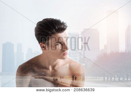 Bright day. Successful handsome model looking away while having splendid photo session against city background