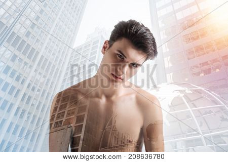 Hidden emotions. Close up of relaxed model with a stylish haircut standing against city background while expressing calmness