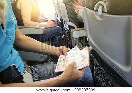 asian male sitting in aircraft with passport and boarding pass in hands