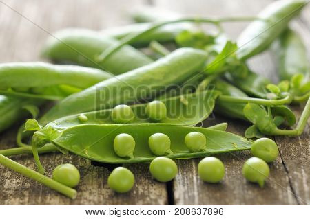 Delicious green peas on a wooden table