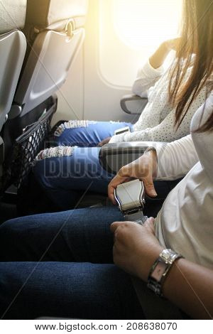 woman hands fasten belts while sitting on airplane seat.