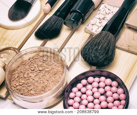 Makeup products and accessories to hide pigmentary imperfections, even out skin tone and complexion: concealer, foundation, powders, blush, make up brushes. Selective focus, retro toning