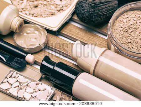 Makeup products for perfect complexion. Concealer, foundation and correcting, bronzing, highlighting powder with make up brushes. Toned image