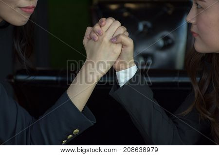 Two serious Asian women  press hands each other /Close-up Of A Two Asian Businesswoman Competing In Arm Wrestling
