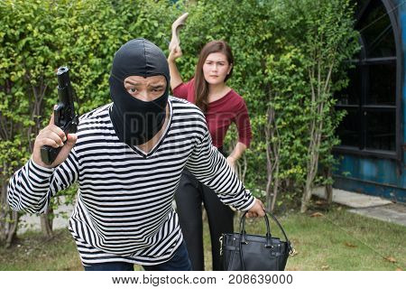 Bandit ran to escape the Asian woman/Armed robber and victim with a handbag ,criminal concept