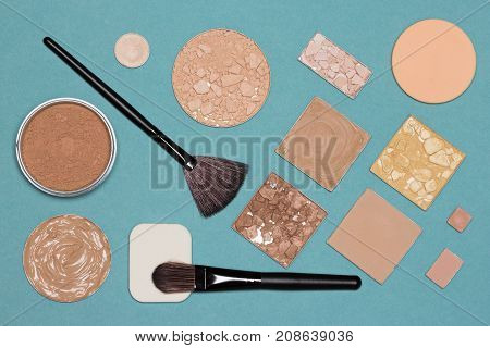 Cosmetic products and accessories for corrective makeup, flat lay still life on blue background