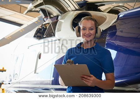 Portrait Of Female Aero Engineer With Clipboard Carrying Out Check On Helicopter In Hangar