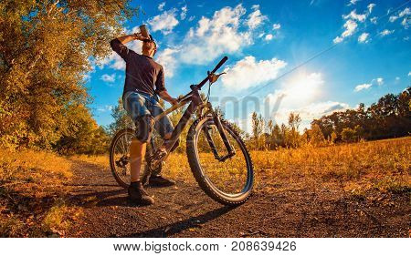 Young Athletic Guy In A Black T-shirt And Baseball Cap On A Sports Bike