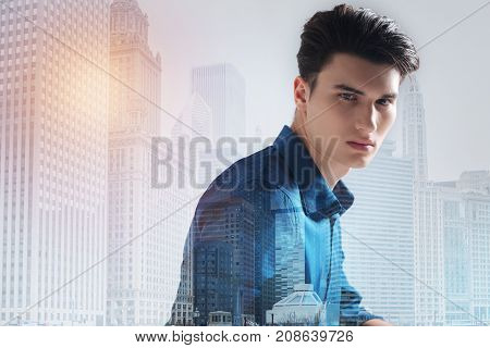 Peaceful day. Close up of calm teenager with a stylish haircut looking at you while standing against city background