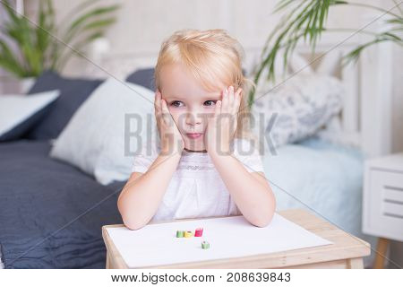 Cute pretty little girl with her hands to her cheeks sitting at a small wooden table drawing on paper looking thoughtfully to the side