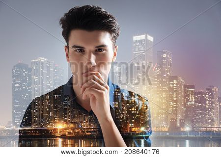 Thinking process. Young handsome model touching his chin with a hand while standing against beautiful city lights