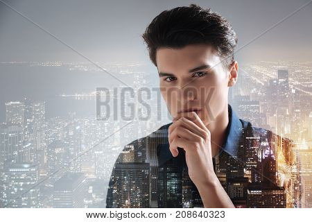 Pleasant evening. Close up of good looking student touching his chin while standing against city background