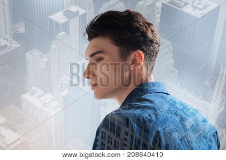 Bright morning. Close up of relaxed teenager looking away while standing against city background