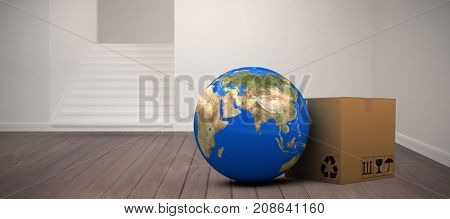 3D planet Earth and cardboard box against white background against empty room
