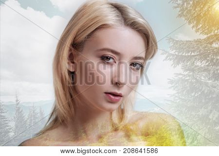 Lovely glance. Close up of beautiful girl looking at you with calmness in her eyes while standing against pleasant nature