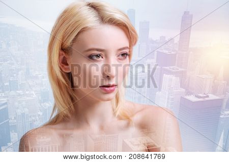 Inborn beauty. Calm lovely girl looking at the distance while standing against beautiful modern buildings