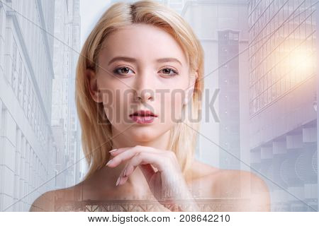 Natural beauty. Close up of adorable model keeping her hand near chin and having sharp glance while standing in urban surrounding