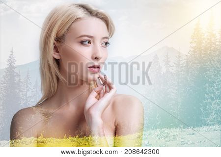 Full of energy. Beautiful model looking away and touching her chin while standing against nature background