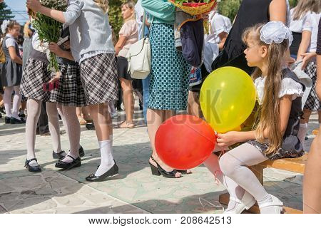 Anana Russia - September 1 2017: The first-grader looks sadly at a meeting of girlfriends on the feast of the first of September