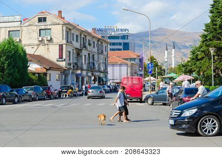 SHKODER ALBANIA - SEPTEMBER 6 2017: Street (Rruga Vilson) Grand Hotel Europa in city center of Shkoder. Unknown people ride bicycles and walk down street