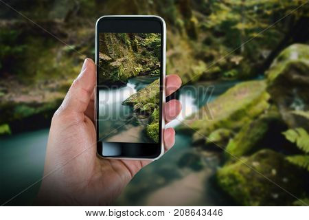 Cropped hand holding smart phone against rapids flowing along lush forest