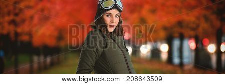 Portrait of woman in winter coat against leaves on field amidst trees