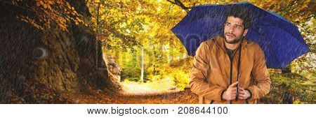 Man standing with blue umbrella against country road along trees in the lush forest