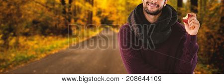 Portrait of young man holding apple against country road along trees in the lush forest