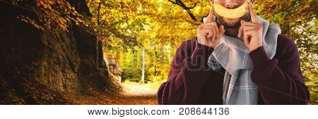 Portrait of man holding banana against country road along trees in the lush forest