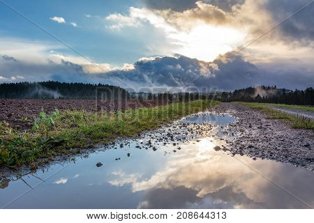 Autumn landscape - Black Forest. Dirt road with puddle after a rainy day at sunset.