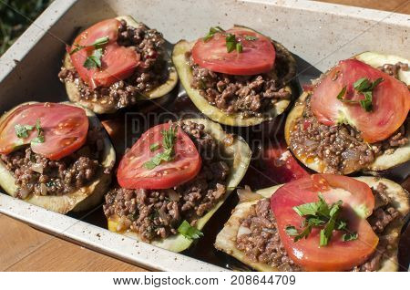 Rustic tray of raw eggplants filled with minced meat and fresh tomato prepared for cooked in oven