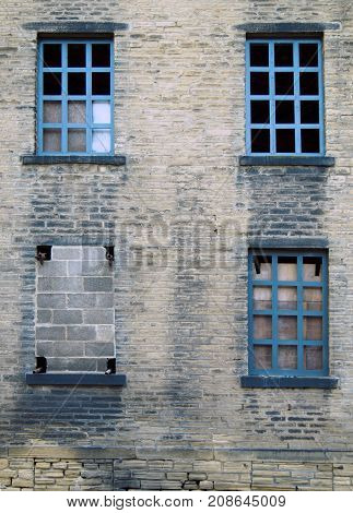 four broken and bricked up windows in a derelict abandoned old house with dirty stained bricks