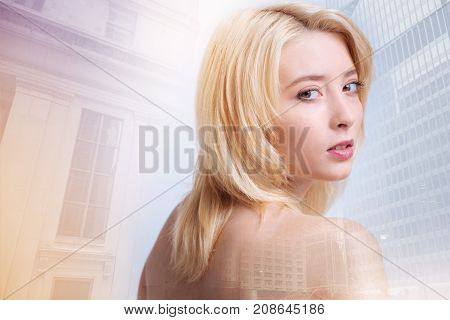 Splendid photos. Pretty young model having mysterious expression on her face while standing against city buildings