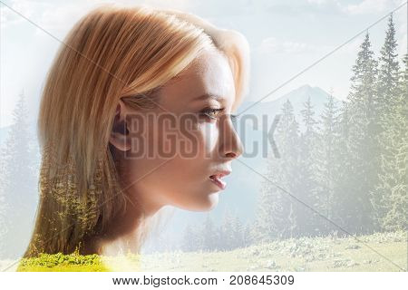 Bright colors. Profile of pleasant girl looking away while standing against beautiful nature background