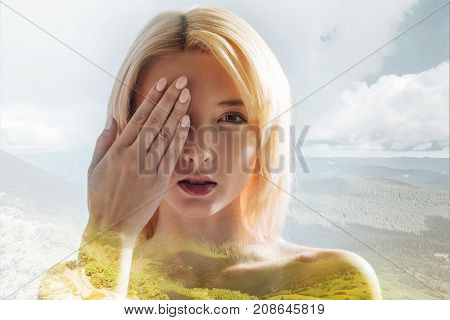 Brilliant appearance. Close up of gorgeous girl keeping her hand in front of her face and hiding the half of it while standing against nature background