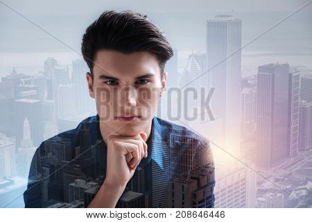 Expressing sadness. Serious handsome model keeping his hand under the chin while standing against city buildings