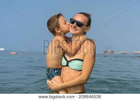 Young mother in black sunglasses and smiling baby boy son in green baseball cap playing in the sea in the day time. Positive human emotions, feelings, joy. Spring and summer holidays.