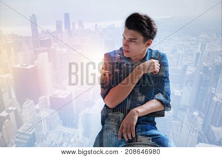 Beautiful city. Waist up of pleasant teenager looking away while spending leisure time in the town