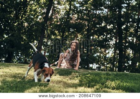 What is there? Cute little girl playing with her dog while crouching outdoors