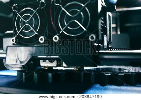 FDM 3D-printer manufacturing spur gears from silver-gray filament on blue print tape - view on print head print bed and chamber- background blanked out blurry